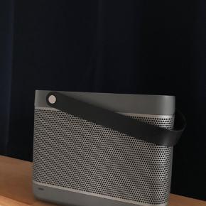 """Rigtig god højtaler fra B&O. Den kan både kobles til via Airplay (wifi) og via kabel (usb eller minijack). Ved tilkobling via usb, bliver den tilkoblede enhed opladt samtidigt.  Fungerer rigtig fint og spiller super godt! Dog rækker batteriet ikke helt til de 6 timer - nærmere de 4 timer.  Eneste lille """"skavank"""", som kan ses på et af billederne er, at lågen bag på ikke kan lukkes helt. Dette ses dog ikke tydeligt."""