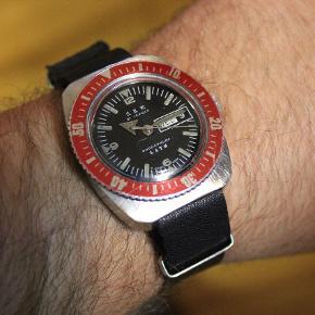 Vintage Sperina dykker ur.  S.B.W. Diver Tropical Vintage Swiss Made herreur.   Day date ur fra 1960erne.  Unikt ur som ikke kan findes andre steder. Så hvis du ønsker dig et dykker ur som er unikt og helt specielt så har du fundet det!   Der garanteres IKKE for at uret er vandtæt da det er et vintage ur.   Uret er mekanisk og skal trækkes op ca 1 gang om dagen. Uret holder tiden og går som det skal. Det er et ældre ur så der garanteres heller ikke for at det kan miste et par minutter i løbet af dagen.  Jeg sælger uret da jeg desværre ikke får det brugt. Uret er et samlerobjekt som sagtens kan bruges til hverdag.   Fantastisk cool ur.  Kommer med en sort læder natorem.