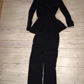 Fint jakkesæt i Viskose, med bindedetalje på blazeren og brede bukseben.  Brugt en gang og vasket.