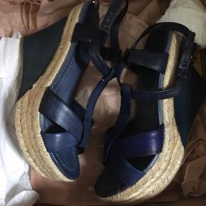 Smukke Miu Miu sandaler i læder med plateau. Desværre kom de ud i regnvejr og farven på den ene tog skade. Reparation med farvet skosværte resulterede i farveforskel på den ene sko. Derfor den lave pris. Ellers i flot stand. Æske medfølger. Og dustbags, hvis jeg kan finde dem. Jeg er en str. 38,5