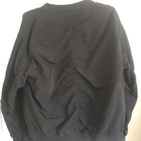 Bomberjakke fra Monki i størrelse M. Brugt meget lidt, har små lommer på det ene ærme og store lommer foran med knaplukning. Lavet af 100% polyester og jakken er derfor et glat stof der holder godt.