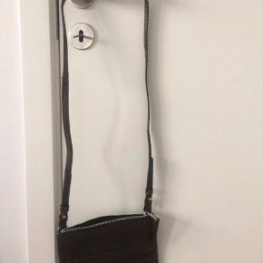 """Jeg sælger min smukke taske fra Tiger of Sweden. Jeg har aldrig brugt den, hvilket også gør at den stadig er lidt """"stiv"""" i materialet - dette vil rette sig ud, når man bruger den, da det er læder.   Kan afhentes i 8000 Aarhus C eller 8783 Hornsyld. Kan også sendes med post"""