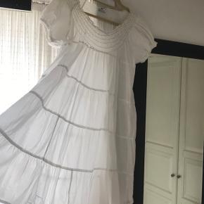 Day kjole i hvid bomuld med smock øverst så det er muligt sætte den ned på skulderen.   Størrelse 42.  Korte ærmer med elastik og små pailletter øverst på smockstykket.  Let og luftig med masser af fylde i skørt med falder let og blødt.  Brugt og vasket 2-3 gange