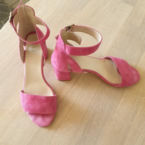 Smukke, klassiske sandaler med hæl i ruskind og spænde om anklen, der er gode at gå i. Kun brugt få gange. Det er modellen May. Hælen er 6.5 cm høj.