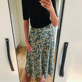 Har denne flotte blomstrede nederdel til salg da jeg ikke får den brugt. Lukkes med lynlås i siden.  Den sorte strop top er også til salg til 50kr. Str 36.
