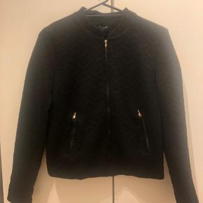 Sort bomberjacket-lignende jakke/trøje med mønster. Har lommer med lynlås lukning. Vasket få gange.