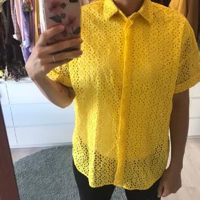Sommer gul skjorte, med korte ærmer og hul mønster. Den er gennemsigtig, og jeg har bare en hvid t-shirt inden under ☺️