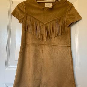 Enkel og rigtig sød kjole i ruskind lignende kvalitet. Med korte ærmer og frynser på brystet. Rund hals med en lille udskæring. Kan bruges også bruges over stramme jeans. I meget pæn stand uden huller og pletter. Ryglængde 66,5 cm, 1/2 brystmål 36 cm, 1/2 hoftemål 40 cm, armlængde 14 cm.