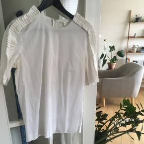 COS kortærmet skjorte med fine detaljer. Lidt gulig under armene derfor pris. Kan sikkert fjernes med rette middel.