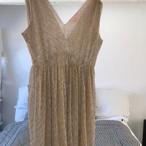 Utrolig smuk Buch Copenhagen kjole med guld/sølv glimmer og plisseret effekt. Kjolen har v-udskæring foran samt på ryggen.  Størrelsen er en small. Kjolen har oprindeligt været længere, men er blevet forkortet ved Buch's egen skrædder. Kjolen er lårkort.  Der er en lille smule glimmer fnuller til højre for brystet, men dette kan klippes forsigtig af med en saks (Se billede nr. 2)