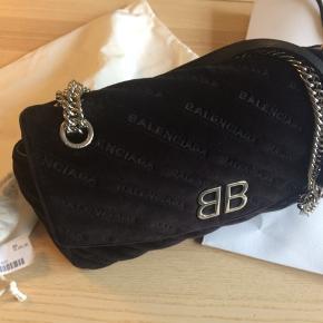 Virkelig lækker Balenciaga som passer til alt. Læder med sort velour udenpå. Godt et år gammel. Købt til 10.075,- og steget siden.  Kæden kan bæres dobbelt over en skulder eller enkelt cross-body.  Den er brugt men passet rigtigt godt på.  Målene er ca. 28x15x8/9 cm.  Se også gerne mine andre annoncer, giver gerne mængde rabat ☺️