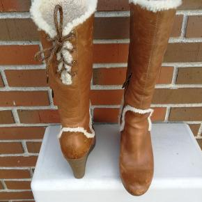 """Flot vinterstøvle i skind købt på Manhattan, New York for ca. 2000 kr..  I hele støvlen er der et dejligt varmt """"bamse"""" foer som går igen som pynt på støvlen. Støvlen snøres bagpå. Støvlehælen er foran 1 cm og hælen 8,5 cm. På udvendig inderside er en robust lynlås. Sælges på grund af graviditet og derfor blevet for små."""