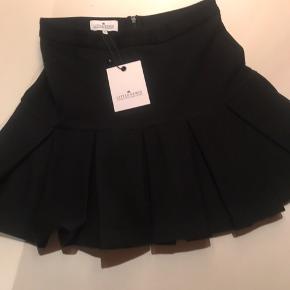 Flot sort nederdel med læg, i kraftig Tencel blanding som gør den falder tungt.   str 12 år Ny og med tags - aldrig brugt