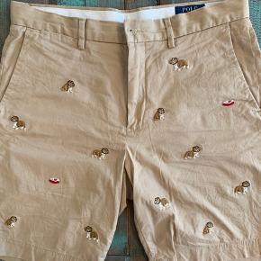Geniale shorts fra Polo Ralph Lauren med all-over broderi af bulldogs mv. str. 32. Brugt få gange. Nypris 1.199,-  Prisen er fast og bytter ikke.
