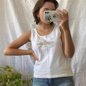 Vintage t-shirt uden ærmer fra Burberry. Størrelse L, men lille i størrelsen og passes bedre af en størrelse S/M. Ses på en størrelse S på billederne.  Se også mine andre annoncer, jeg giver mængderabat🧚🏼♀️✨  Søgeord: vintage, retro, genbrug