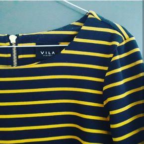 Mørkeblå kjole med gule striber fra Vila, str. S. Lårkort, med trekvart lange ærmer og lukkes med guld farvet lynlås i ryggen. Blødt og kraftigt stof i polyester, viskose og elastan. Meget pæn og velholdt/nærmest som ny - kun brugt og vasket en enkelt gang. Pris: 75 kr plus porto