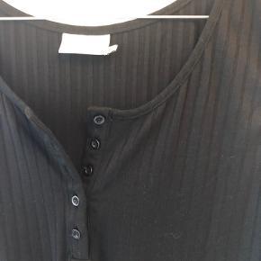 Basis top i grov rib og med stolpe lukning foran som detalje. Rund hals og brede stropper.