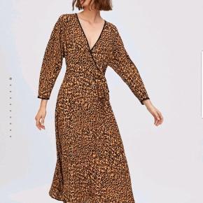 """Slå-om kjole i leopardmønster. Den går mig til midt på skinnebenet (jeg er 1.78 m). Der er lynlås i siden, så den kan ikke """"gå op"""" når man har denne. 100% viscose. Den skal lige stryges og så er den klar til brug."""