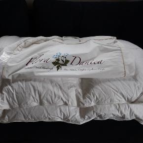 """Lækker """"Flora Danica"""" dyne i 100% """"moskusdun"""", str. 135 x 200 cm. fra serien """"Tusindfryd"""". Vægt 800 gram og bæreevne 11. Dynen der aldrig har været brugt, har en nypris på kr. 3.699."""