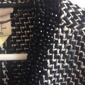 Lidt oversize jakke fra h&m med perler rundt i kanten ved halsen. Nogle af perlerne er faldet af eller hænger lidt, hvilket afspejler prisen. Nypris 600.