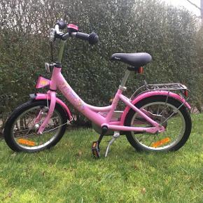 """Lækker PUKY 16"""" pigecykel i lyserød. Købt i 2017. Cykellygter medfølger. Defekt refleks ved bagagebærer. Ellers fejler cyklen intet og kører godt."""