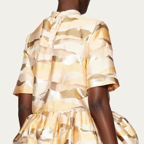 Str L/40 Aldrig brugt fra new AW kollektion   BYD  Tolu Top in Horizon Gold. A feminine peplum top with short sleeves. Featuring a round neckline with a stand collar and draping details. The print features blush tones of peach and yellow and a metallic gold. Open loop closure at back. Add a scrunchy in Horizon Gold for detail.