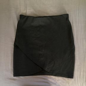 Fin nederdel fra Gina Tricot med elastikbånd i taljen. Den fremstår mindre sort på billedet end den er