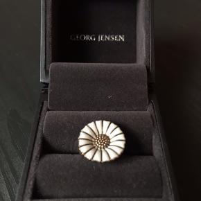 Den klassiske marguerit ring fra Georg Jensen i mellem størrelsen. Den har en mini flig slået af det ene blad, hvilket kun ses meget lidt. Den er nogle år gammel, men jeg har kun brugt den da den var helt ny. Guldet er falmet lidt af at ringen har ligget i skuffen. Original kasse medfølger, men den er dog lidt i stykker.  Det er svært at tage helt skarpe billeder af smykker med en iphone😅 Så skriv endelig hvis du er interesseret i at se nogle flere! Ringen er ca. 5,5 cm hele vejen rundt.  Jeg er åben overfor bud☺️