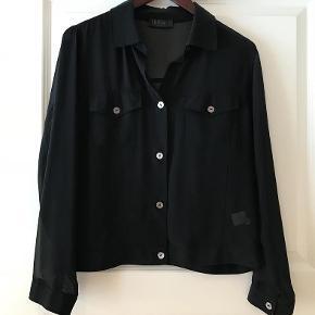 """Varetype: Transparant jakke/bluse Farve: Sort  Fin kort """"jakke"""" fra Fransa.   100% polyester Brystvidde 2x53 cm. Længde 56 cm.   TRYK PÅ """"KØB NU"""" FOR AT SIKRE DIG HANDLEN :-)"""