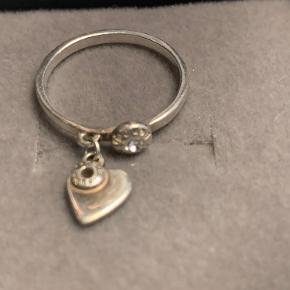 Fin ring med hjerte vedhæng fra Henri Bendel.  Str. 51-52 svarende til en small.