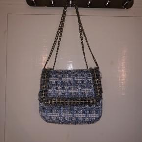 Vores fine boucle skuldertaske Waterlik Loel Bag kan bruges på tværs af trends og sæsoner. Denne skuldertaske er designet med kæderem, som både kan bruges crossbody samt gøres kortere, skuldertasken er forret og og har inderlomme. Boucle bag Kæderem Crossbody