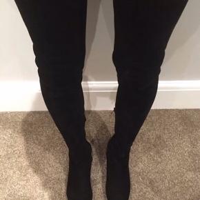 Knælange støvler i sort i ruskind. Kun brugt én gang.