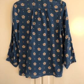 Smuk blå skjortebluse fra Edith&Ella med hvide/orange blomster og fine detaljer. Kan også sagtens passes af en str. S. Aldrig brugt, mærke sidder stadig i.