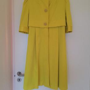 Frakke med 3/4 ærmer, knapper og stor aftagelig sløjfe. Brugt få gange.