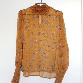 Sød semitransperant bluse i orange-gul med blå blomster. Vaskemærkaten er klippet af.