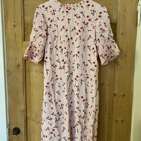 En rigtig fin rosa kjole med små røde blomster. Passer en str. S/M.
