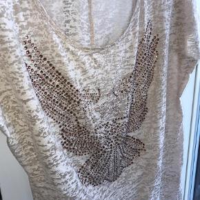 Varetype: T-shirt  Størrelse: S/M Farve: Beige Oprindelig købspris: 249 kr. Kvittering haves.  Super lækker T-shirt sælges. Aldrig brugt, og bon haves. Kom med et bud. Eller kom forbi og kig. Jeg har meget tøj i samme stil. Jeg kan kontaktes på 42422704