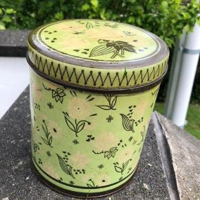 Flot grøn, vintage kagedåse med flot blomstermønster i lys og brun. Dåsen er god både til opbevaring, men er også flot som pyntegenstand i hjemmet. Dåsen er i rimelig god stand, men med patina. Højde: knap 18 cm. Diameter: 15,5 cm.