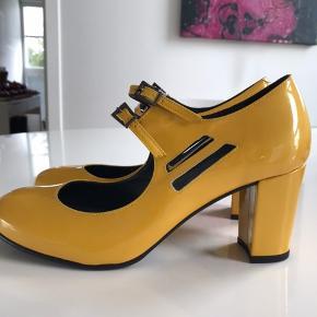 Fede lak sko i Metallic varm gul farve. Hælhøjde ca 7 cm. Sko æske medfølger.