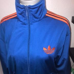 Retro vintage Adidas firebird i størrelse small, men stor i størrelsen, turkis med orange striber. Lynlås ned foran, købt i episode. Ved køb af flere ting kan der opnås mængderabat