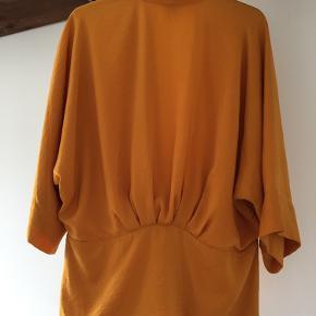 Brugt 1 gang. Str S/M. Klar okkergul orientalsk inspireret top/kimono med hægtelukning og 3/4 ærmer. Polyester.  Se også mine andre annoncer :)