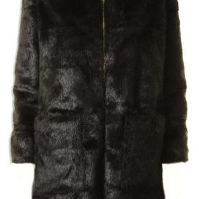 Skønneste sort fake pels fra Sofie Schnoor. Frakken fra Sofie Schnoor er syet i en lækker sort fake og har en dejlig hætte.  Helt ny og med mærke på endnu.