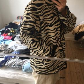 Mega fed zebra farvet jakke, som ikke er denim, men noget andet materiale. Den er god og luftig så man kan have en anden trøje inden under. Desuden kan den vendes, så mønstret skifter lidt. Se billede 3.