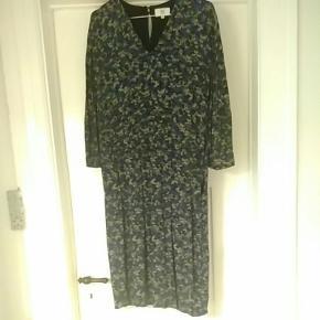 Kjolen sidder til i taljen. Har skjulte lommer og fine knapper i det øverste af ryggen. Kjolen går ca. til knæet. Kjolen er brugt to gange.