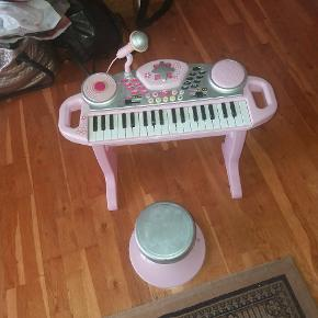 Keyboard med masser af effekter. Mikrofon til at synge med. Enkelte toner hænger - men ellers i god stand. Stol medfølger