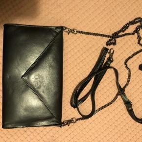 Cool taske i en grå/blå farve med metallic skær. Har to remme med. Mål 26 x 16 cm