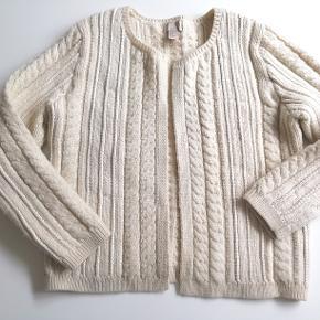 Bytter ikke! Eksklusiv porto. Lækker strik trøje fra H&M str. 42. Trøjen har strik mønster. En enkelt hægte som lukketøj.  For og bag stykket målt ved bryst linjen 116 cm. Længde fra skulder og ned 62 cm Ærme længde fra skulder og ned til håndled 64 cm Skulder søm 12 cm. 67% Uld, 20% Bomuld, 3% Acrylic, 2% Polyamid. Farve: Creme  Trøjen fremstår i pæn stand, har kun været brugt en enkelt gang, fremstår som ny. Kommer fra et ikke ryger hjem.