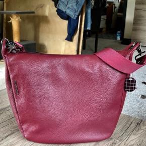 Flot Mandarina Duck taske i rødt blødt læder. Meget rummelig. Aldrig blevet brugt, derfor sælges den. L. 30 x H. 29 x B. 10 cm.  Rem 140 cm ialt. Prisen er fast, da det er under 1/2 pris, og stadig ubrugt. Sender gerne mod betaling af porto, samt TS gebyrer.