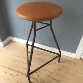 Barstol i samme stil som gamle skolestole med metalben og lædersæde i patineret cognacfarvet læder. Diameter på sædet er 35cm og siddehøjden er 70cm.