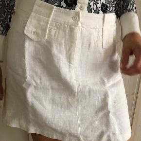 """Chick, kort, A-formet nederdel fra italienske LIST.  Med herlige detaljer (se billeder).  Størrelse. ca. 38 Farve: Hvid Materiale: Hør  """"Modellen"""" på billederne er 176cm høj, 65 kg  Pris: 110 EUR = ca. 825 kr.  Købt i Rom. Ny/aldrigt brugt. I perfekt stand."""